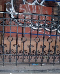 Old wrought iron fence with lovely curlicues and details AND graffitti!